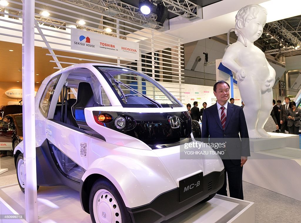 Japan's auto giant Honda Motor president Takanobu Ito displays the company's new micro commuter 'MC-Beta' as they started field tests with Japan's three cities at the press preview of the Tokyo Motor Show in Tokyo on November 21, 2013, next to a replica of the famous Brussels statue 'Manneken-Pis' as a way to illustrate the fuel cell technology. The 43rd Tokyo Motor Show, which runs until December 1, features 177 exhibitors including parts suppliers from a dozen countries. AFP PHOTO / Yoshikazu TSUNO