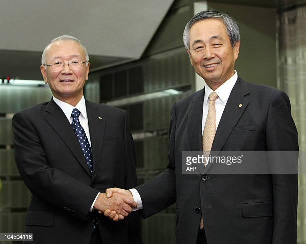 Japan's auto giant Toyota Motor executive vice president Yoichi Ichimaru shakes hands with Toyota's subsidiary Daihatsu president Koichi Ina as they...