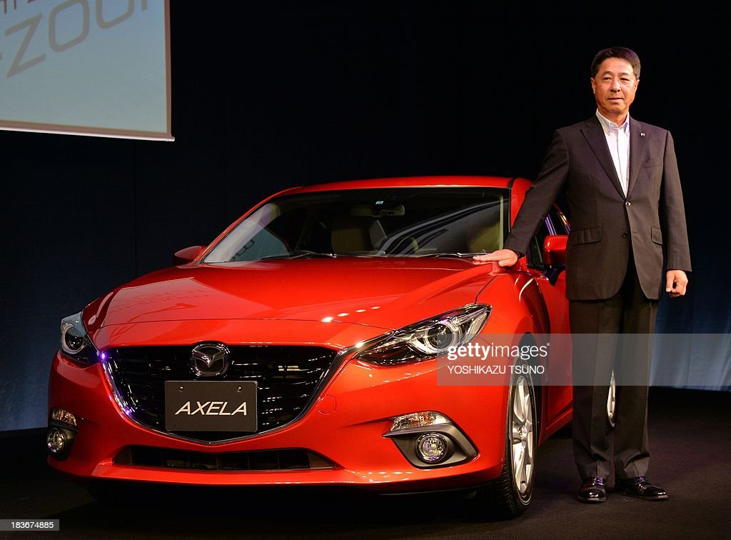 Japan's automaker Mazda president Masamichi Kogai introduces the new compact vehicle 'Axela', known overseas as 'Mazda 3', in Tokyo on October 9, 2013. The new Axela is equipped with a 1.5-litter or 2.0-litter gasoline engine or 2.2-litter turbo charged diesel engine or 2.0-litter gasoline-electric motor hybrid engine to drive sedan or hatchback body. Mazda will put it on the market on November 21. AFP PHOTO / Yoshikazu TSUNO
