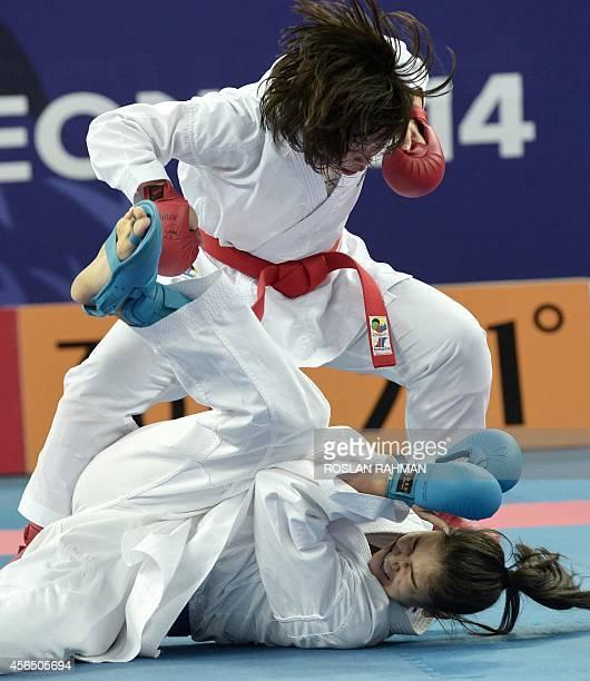 Japan's Ayumi Uekusa punch down against Uzbekistan's Khilola Badalova in the Karate kumite women's 68kg quarterfinals in Gyeyang gymnasium in Incheon...