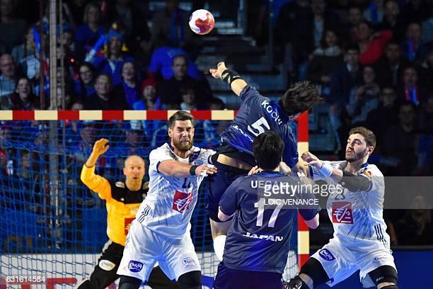 Japan's back Kairi Kochi attempts a shot on goal over France's pivot Luka Karabatic and France's pivot Ludovic Fabregas during the 25th IHF Men's...