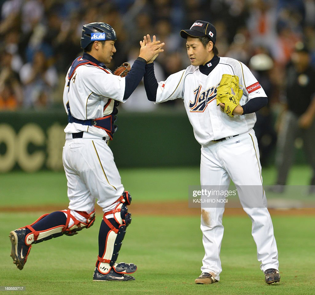 Japan's battery, pitcher Kazuhisa Makita (R) and catcher Ryoji Aikawa (L) celebrate their win over the Netherlands after the 9th inning of the second-round Pool 1 game in the World Baseball Classic tournament at Tokyo Dome on March 12, 2013. Japan beat the Netherlands 10-6.