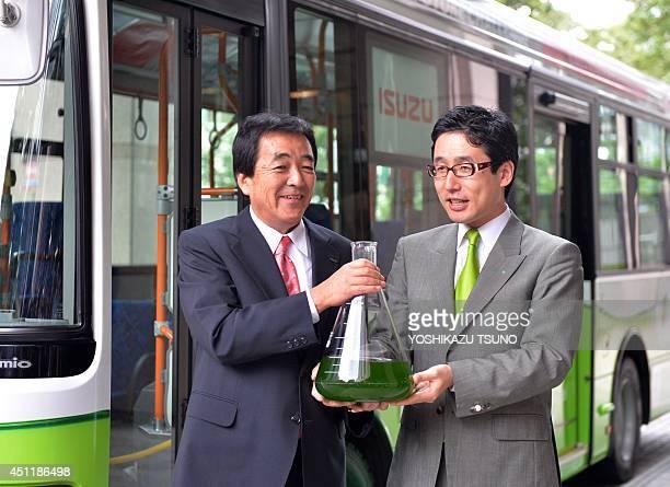 Japan's biotechnology venture Euglena president Mitsuru Izumo and automaker Isuzu Motors president Susumu Hosoi display euglena in a flask at Isuzu's...