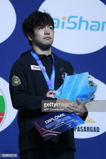Japan's bronze medallist Yuhi Fujinami poses on the podium during the medal ceremony for the men's freestyle wrestling 70kg category at the FILA...