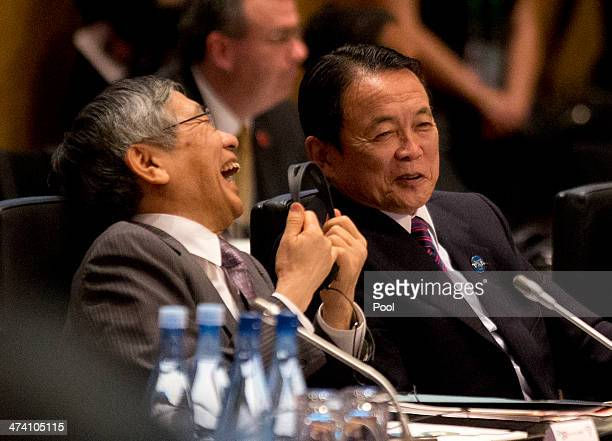 Japan's Central Bank Governor Haruhiko Kuroda laughs alongside Japan's Minister of Finance Taro Aso during the opening session of the the G20 Finance...