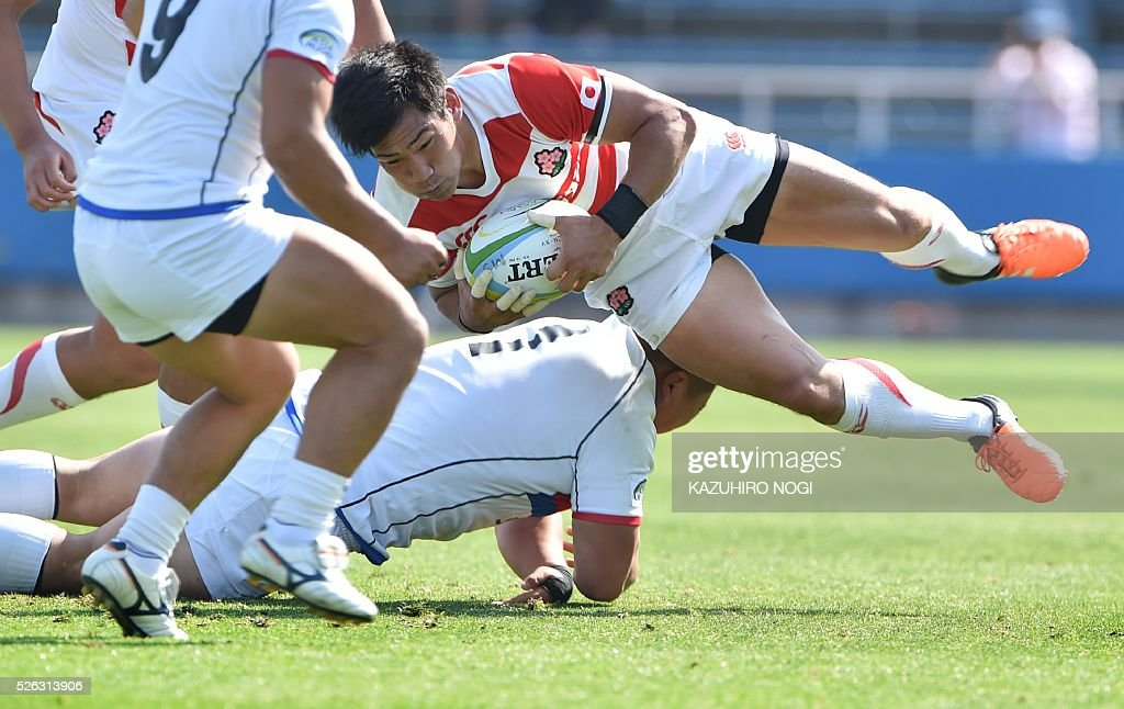Japan's centre Ryoto Nakamura (R) is tackled by South Korea's prop Na Kwanyoung (bottom) during their Asian Rugby Championship rugby match in Yokohama on April 30, 2016. / AFP / KAZUHIRO