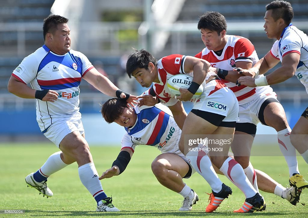 Japan's centre Ryoto Nakamura (C) keeps the ball against South Korea during the Asian Rugby Championship rugby match in Yokohama on April 30, 2016. / AFP / KAZUHIRO
