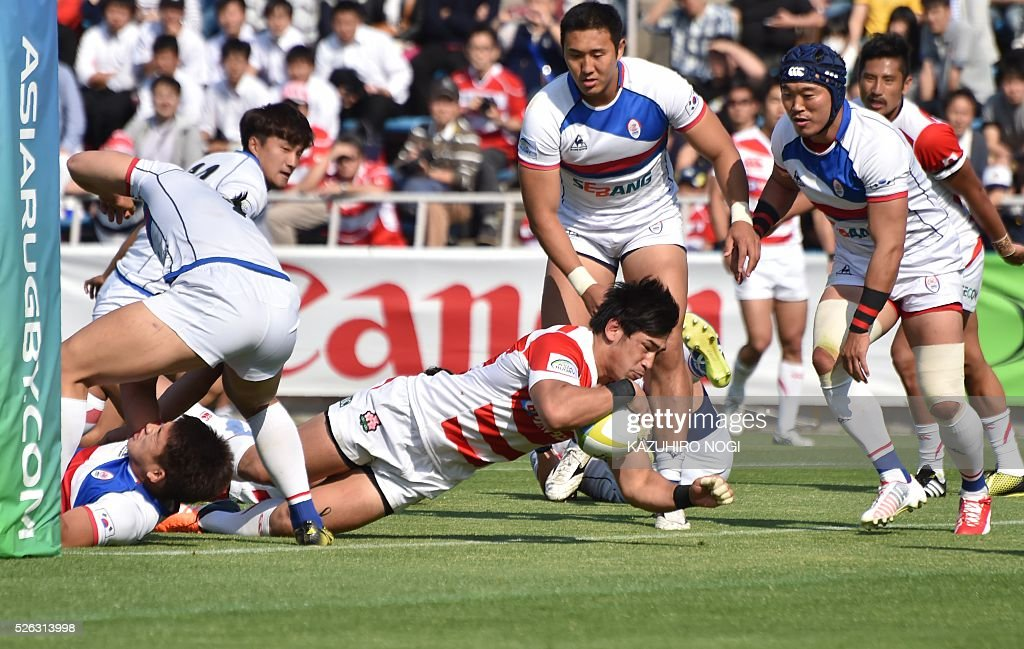 Japan's centre Ryoto Nakamura (C) scores a try against South Korea during their Asian Rugby Championship rugby match in Yokohama on April 30, 2016. / AFP / KAZUHIRO