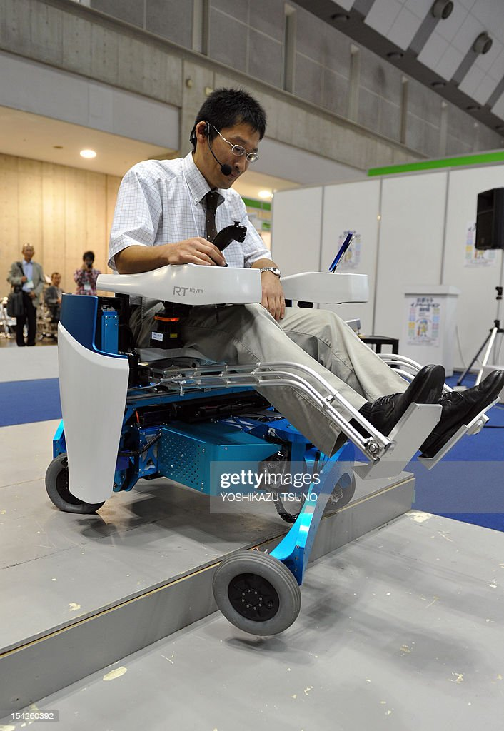 Japan's Chiba Institute of Technology associate professor Shuro Nakajima demonstrates how to use a robotic wheelchair called the 'RT-Mover' which enables a user to climb 25cm gaps and move in omni-directions, at a demonstration during the Japan Robot Week exhibition in Tokyo on October 17, 2012. The wheelchair, which operates at a maximum speed of 5.4kph, can move over uneven ground covering gaps of a maximum of 25 cm (10 inches) while the user keeps level at all times. AFP PHOTO / Yoshikazu TSUNO