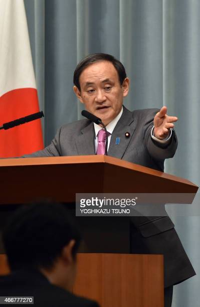 Japan's Chief Cabinet Secretary Yoshihide Suga points to a journalist at a press conference at the prime minister's official residence in Tokyo on...