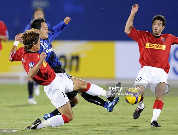 Japan's club team Gamba Osaka midfielder Takahiro Futagawa fights for the ball with Urawa Red Diamonds midfielder Takahito Soma and midfielder Robson...