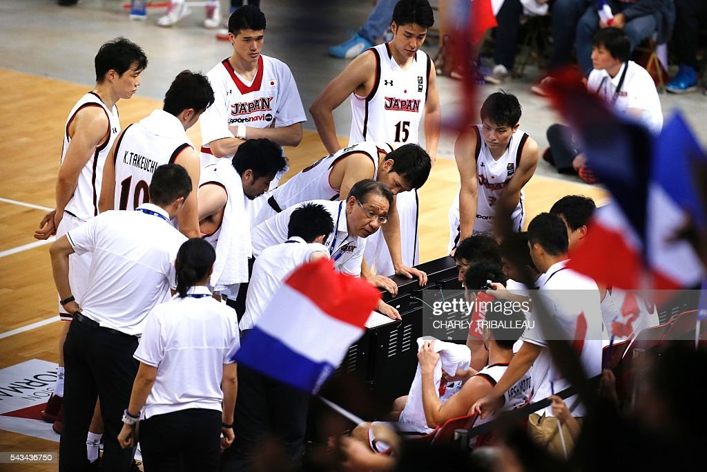 Japan's coach Kenji Hasegawa talks to his players during the basketball match between France and Japan at the Kindarena hall in Rouen on June 28, 2016. / AFP / CHARLY