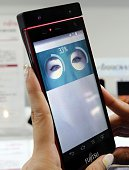 Japan's computer giant Fujitsu employee displays the prototype model of a smartphone with iris authentication system which enables it to identify the...