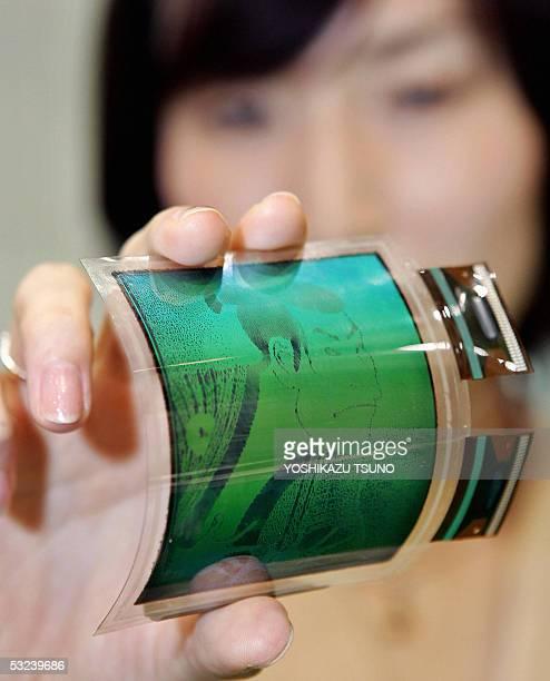 Japan's computer giant Fujitsu employee Sachiko Iino displays a prototype model of an electronic paper display filmbased flexible monocolor LCD...