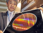 Japan's computer giant Fujitsu researcher Aiichiro Inoue displays a 300mm wafer world's fastest CPU chips 'Venus' with an eightcore Sparc64...