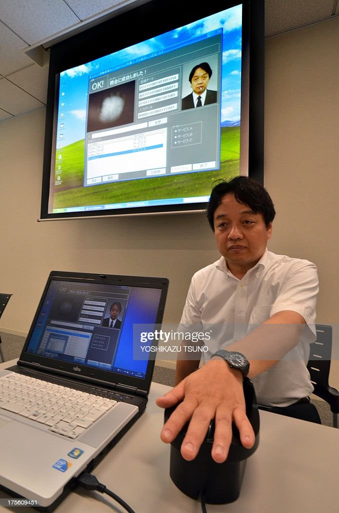 Japan's computer giant Fujitsu researcher Takashi Shinzaki demonstrates the new biometric coding technology for extracting and matching 2,048-bit binary codes from palm vein images at the company's headquarters in Tokyo on August 5, 2013. Fujitsu developed the new technology to create multiple binary codes from a single piece of biometric data such as palm vein pattern. Different binary codes can be used for different biometric authentication services. Fujitsu is expecting to commercialize the new biometric coding technology in 2015. AFP PHOTO / Yoshikazu TSUNO