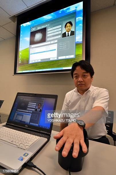 Japan's computer giant Fujitsu researcher Takashi Shinzaki demonstrates the new biometric coding technology for extracting and matching 2048bit...