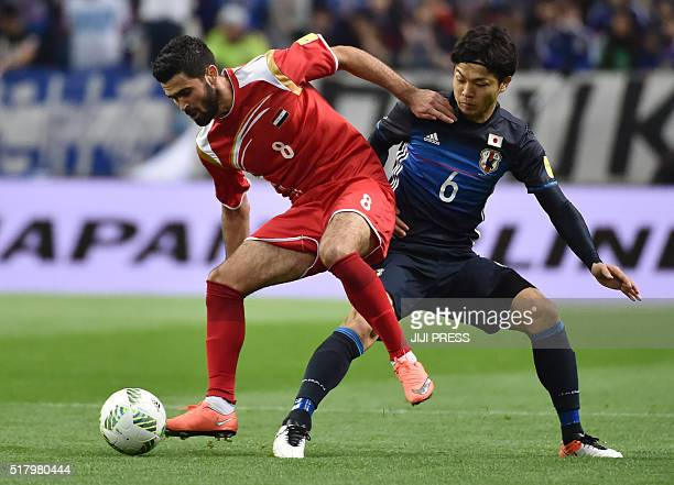 Japan's defender Masato Morishige and Syria's midfielder Zahir Algunami Almedani fight for the ball during the 2018 World Cup qualifier Asian...