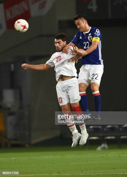 Japan's defender Maya Yoshida battles for the ball with Syria's midfielder Khaled Almbayed during their friendly football match at Tokyo Stadium in...