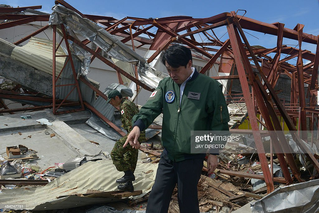 Japan's Defense Minister Itsunori Onodera inspects a damage warehouse in Tacloban on December 8, 2013, which was devastated by Super Typhoon Haiyen that hit the central Philippines on November 8. The super typhoon has left almost 7,000 dead and missing after its rampage through the central Philippines in November. AFP PHOTO / Jay DIRECTO