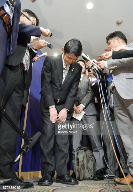 Japan's disaster reconstruction minister Masahiro Imamura bows in apology while speaking to reporters at a hotel in Tokyo on April 25 following his...