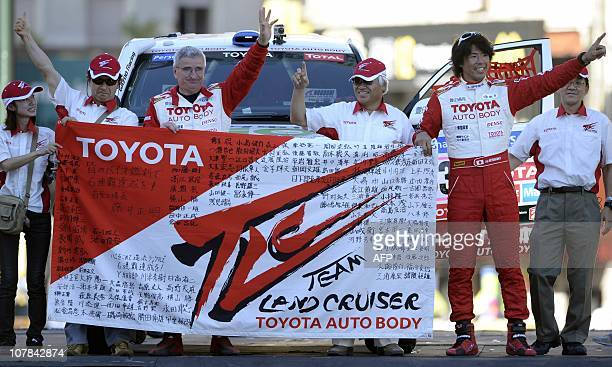 Japan's driver Jun Mitsuhashi and French codriver Alain Guehennec pose with teammates in front of their Toyota on the podium of the symbolic start of...