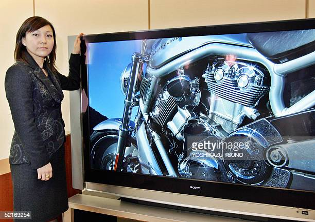 Japan's electronics giant Sony employee displays the new 70inch rearprojection TV set 'QUALIA 006' featuring three fullHD spec reflection LCD panels...