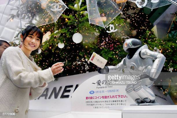 Japan's electronics giant Sony's entertainment robot 'Qrio' and actress Satomi Ishihara in a symbolic gesture during the yearend charity ceremony at...