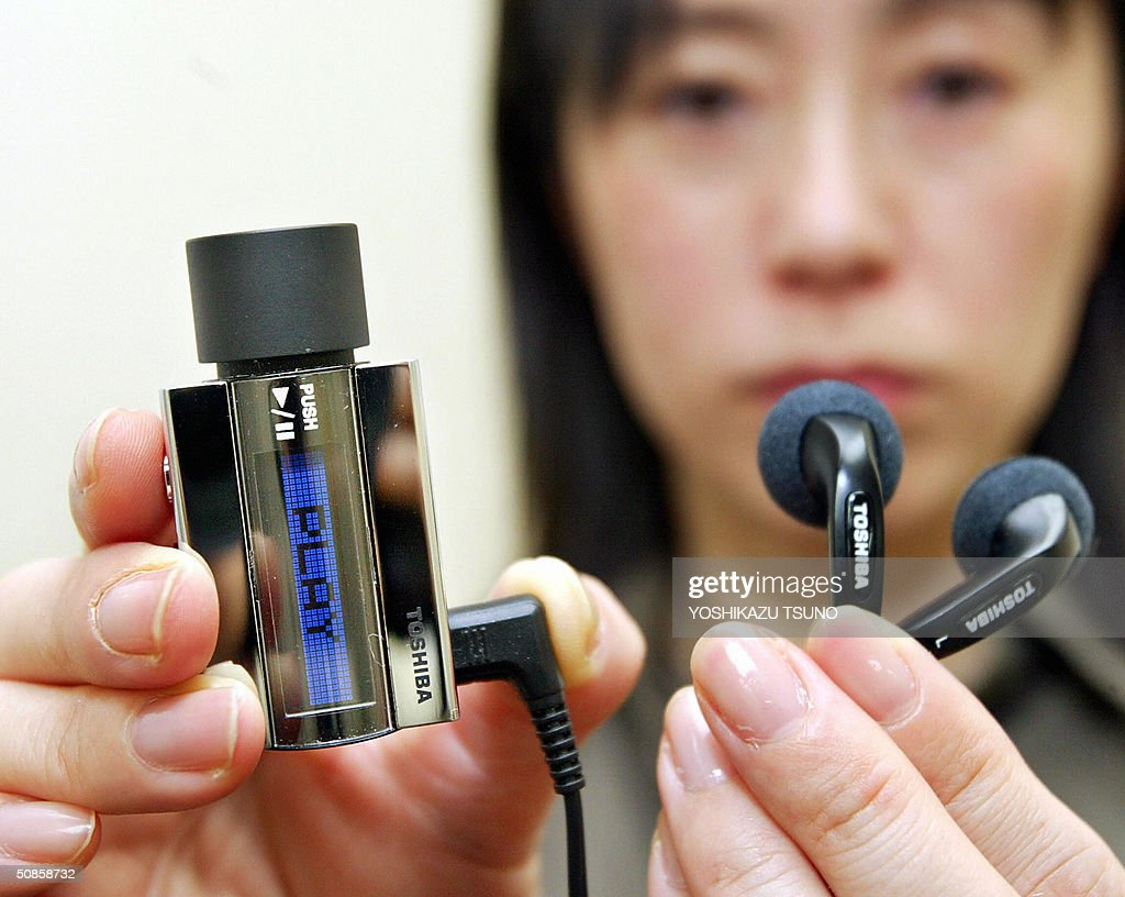 Japan's electronics giant Toshiba employee Junko Furuta displays prototype model of a super compact audio player, equipped with the world's smallest 0.85-inch 4GB hard disk to store some 1,000 music titles at the company's headquarters in Tokyo 20 May 2004. This model is a design study model and not mass produced. AFP PHOTO / Yoshikazu TSUNO