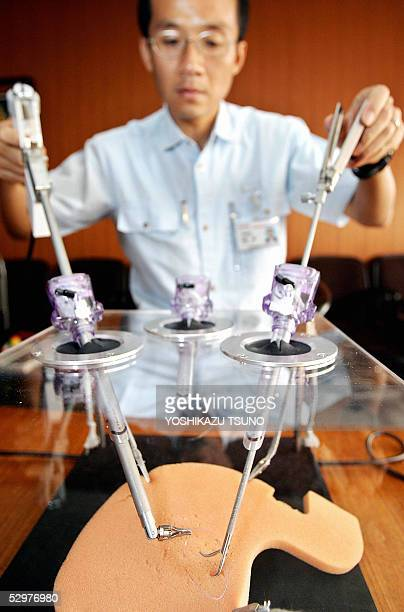 Japan's electronics giant Toshiba researcher Makoto Jinno demonstrates a robotic manipulating force for microsurgery equipped with three servo motors...