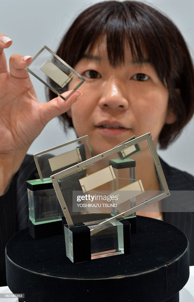 Japan's electronics parts maker Kyocera employee displays the world's thinest film type speaker 'smart sonic sound', using a piezoelectric device (the white part in center) and one mm thickness, including a resin base (the transparent part), at a preview of the Ceatec electronics trade show in Chiba, suburban Tokyo on September 30, 2013. Asia's largest electronics trade show Ceatec will open on October 1, 2013 through October 5 to exhibit the latest electronics technology and products. AFP PHOTO / Yoshikazu TSUNO