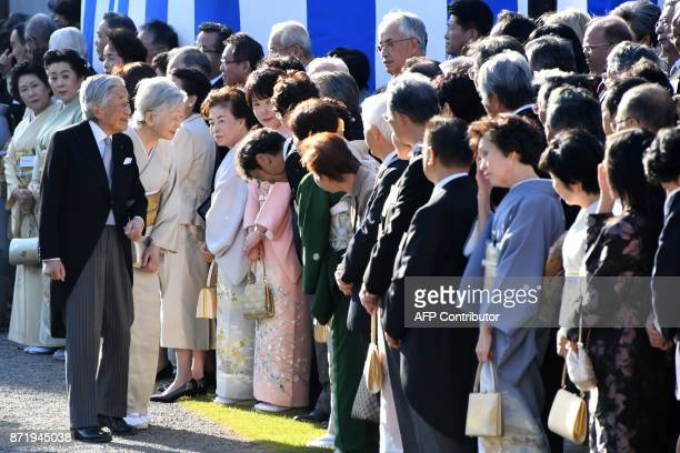 Japan's Emperor Akihito and Empress Michiko greet guests during an Imperial garden party at Akasaka Palace Imperial garden in Tokyo on November 9...