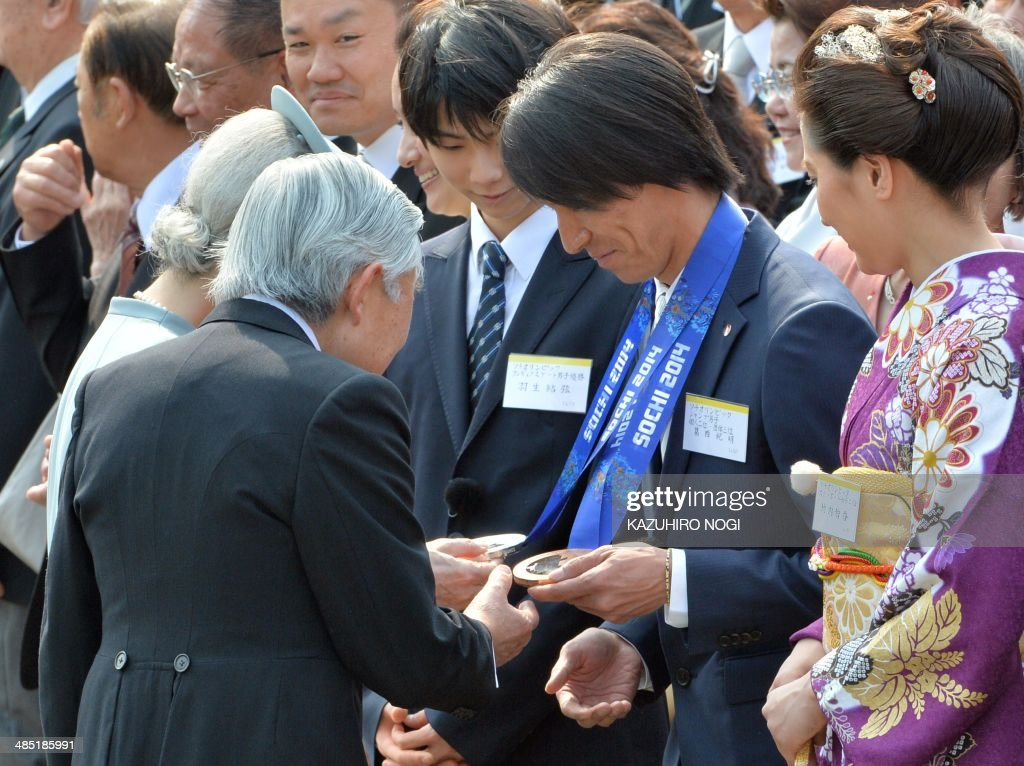 Japan's Emperor Akihito (L) and Empress Michiko (rear L) look at medals of Japanese athlete Noriaki Kasi (2nd R) who captured silver and bronze medals at the Sochi Olympics ski jumping competitions, during the annual spring garden party at the Akasaka Palace imperial garden in Tokyo on April 17, 2014. AFP PHOTO / KAZUHIRO NOGI