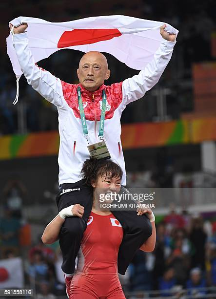Japan's Eri Tosaka celebrates with her coach after winning against Azerbaijan's Mariya Stadnyk in their women's 48kg freestyle final match on August...