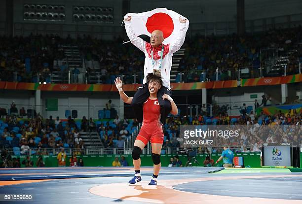 Japan's Eri Tosaka celebrates with her coach winning against Azerbaijan's Mariya Stadnyk in their women's 48kg freestyle final match on August 17...