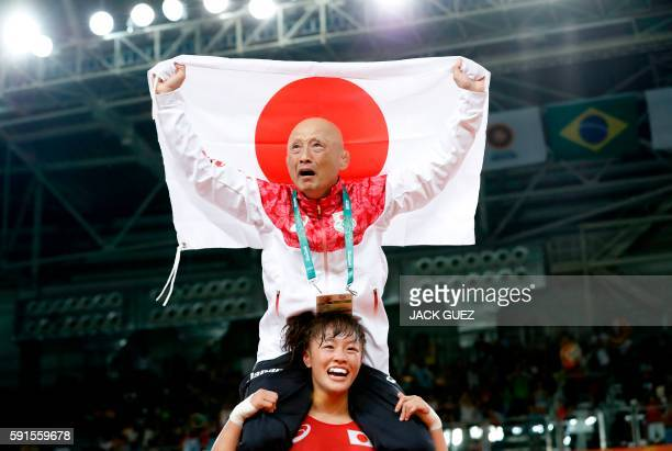 TOPSHOT Japan's Eri Tosaka celebrates with her coach winning against Azerbaijan's Mariya Stadnyk in their women's 48kg freestyle final match on...