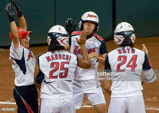 Japan's Eri Yamada celebrates after her fourth inning homerun with teammates Rie Sato and Satoko Mabuchi hit off a hit off a pitch by Cat Osterman in...