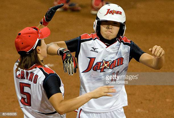Japan's Eri Yamada celebrates after her fourth inning homerun with teammate Ayumi Karino hit off a hit off a pitch by Cat Osterman in their gold...