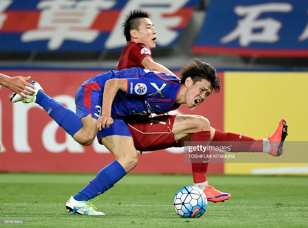 Japan's FC Tokyo defender Kento Hashimoto (L) fights for the ball with China's Shanghai SPIG forward Wu Lei (R) during the AFC champions league round of 16 first match in Tokyo on May 17, 2016. / AFP / TOSHIFUMI