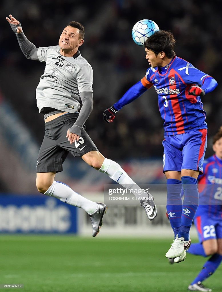 Japan's FC Tokyo defender Masato Morishige (R) heads the ball beside Thailand's Chonburi FC forward forward Rodrigo Vergilio (L) during the AFC champions league play-off match in Tokyo on February 9, 2016. AFP PHOTO / TOSHIFUMI KITAMURA / AFP / TOSHIFUMI KITAMURA