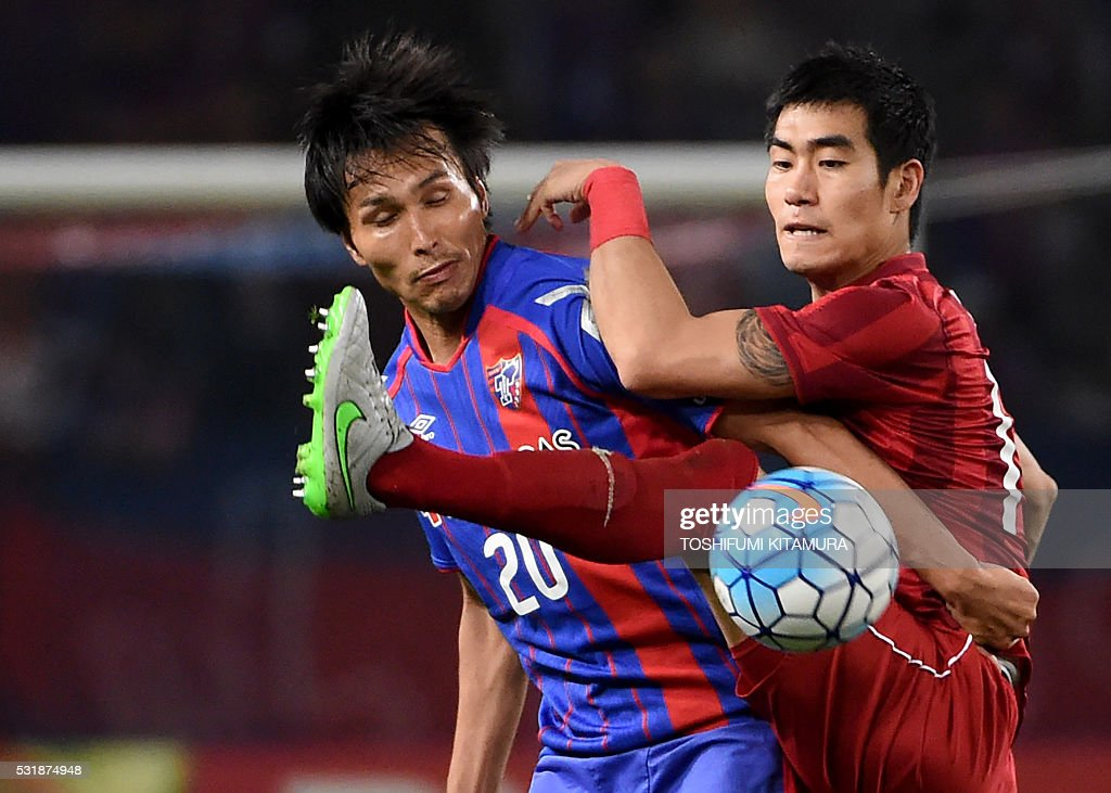 Japan's FC Tokyo forward Ryoichi Maeda (L) fights for the ball with China's Shanghai SPIG defender Kim Ju-Young (R) during the AFC champions league round of 16 first match in Tokyo on May 17, 2016. / AFP / TOSHIFUMI