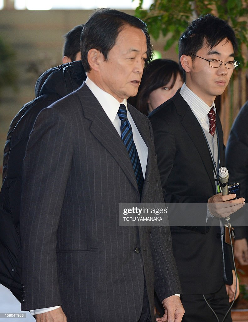 Japan's Finance and Deputy Prime Minister Taro Aso (L), who is also in charge of hostage issues in Algeria, is surrounded by journalists upon his arrival at the prime minister's official residence in Tokyo to attend a cabinet-level meeting to co-ordinate its response to events in North Africa on January 18, 2013. Japanese plant builder JGC said on January 18 it had confirmed the safety of three of its Japanese staff and one Philippine employee in Algeria, with the whereabouts of 74 other staff of various nationalities unknown. AFP PHOTO/Toru YAMANAKA