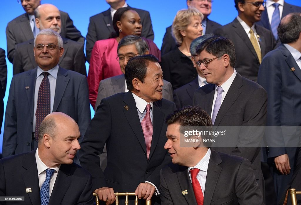 Japan's Finance Minister Taro Aso (C) chats with US Treasury Secretary Jacob Lew before the G-20 Finance Ministers and Central Bank Governors family photograph during the World Bank/IMF Annual Meetings in the International Monetary Fund Headquarters on October 11, 2013 in Washington, DC. At front row are Russian Finance Minister Anton Siluanov (L) and Mexico's Undersecretary of Finance and Public Credit Fernando Aportela Rodríguez. AFP PHOTO/Mandel NGAN