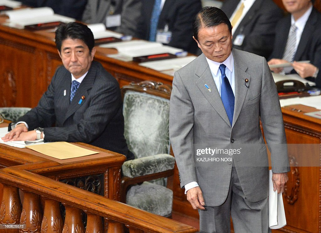 Japan's Finance Minister Taro Aso (R) steps up to the podium to make a speech as Prime Minister Shinzo Abe (L) looks on in the lower house plenary session at parliament in Tokyo on February 4, 2013. Japan's cabinet January 29 approved a 1.02 trillion USD annual budget with boosts in defence and public works spending amid a festering territorial row with China and a renewed assault on deflation.