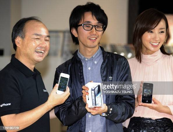 Japan's first buyer of the Apple iPhone 4S receives the smartphone handset from Japanese mobile communication giant Softbank president Masayoshi Son...