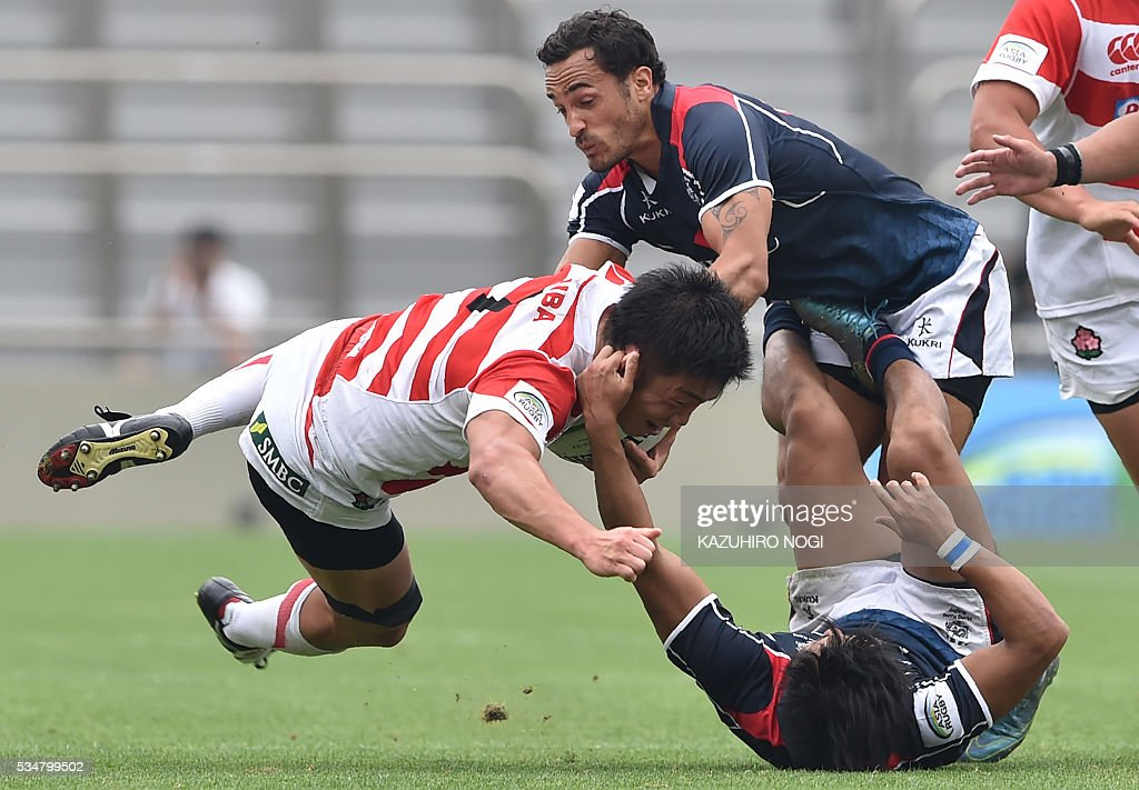 Japan's flanker Shokei Kin (L) is tackled by Hong Kong's scrum half Cado Lee (bottom) and fly half Benjamin Rimene (R) during their Asia Rugby Championship match at the Prince Chichibu Memorial Rugby Ground in Tokyo on May 28, 2016. / AFP / KAZUHIRO