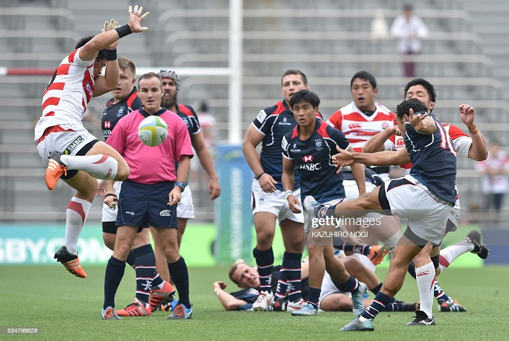 Japan's fly half Ryoto Nakamura (L) blocks the ball kicked by Hong Kong's fly half Benjamin Rimene (R) during their Asia Rugby Championship match at the Prince Chichibu Memorial Rugby Ground in Tokyo on May 28, 2016. / AFP / KAZUHIRO