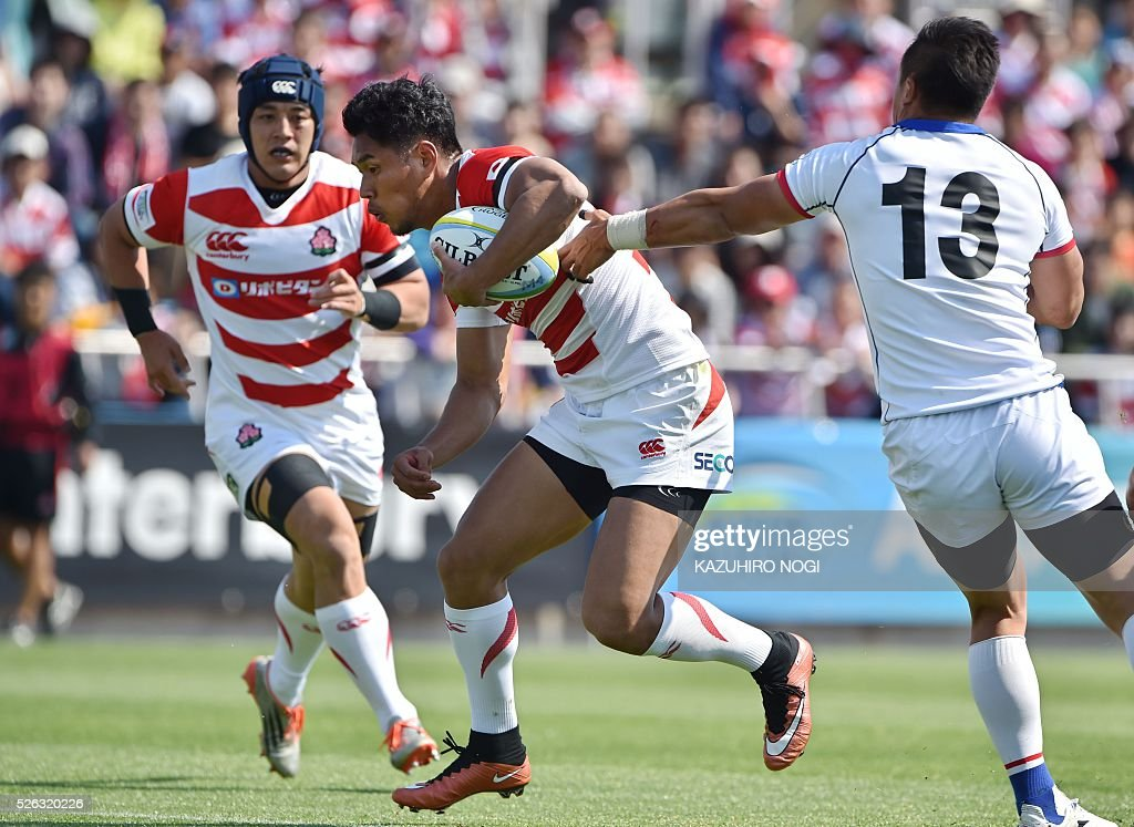 Japan's fly-half Ryohei Yamanaka (C) keeps the ball against South Korea during their Asian Rugby Championship rugby match in Yokohama on April 30, 2016. / AFP / KAZUHIRO