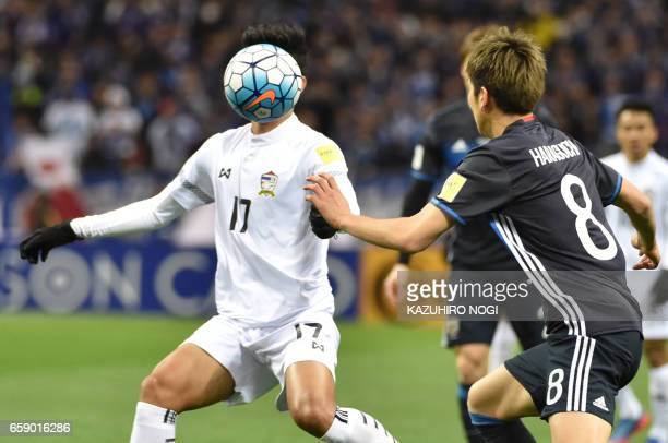 Japans forward Genki Haraguchi and Thailand's defender Tanaboon Kesarat fight for the ball during group B World Cup 2018 qualifying football match...