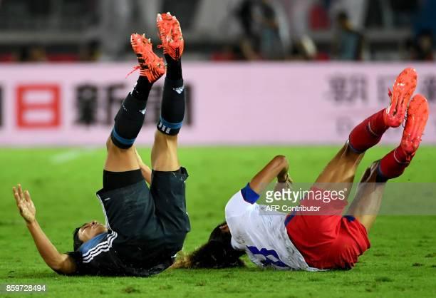Japan's forward Yoshinori Muto and Haiti's midfielder Zachary Herivaux fall on the pitch during their friendly football match at Yokohama on October...